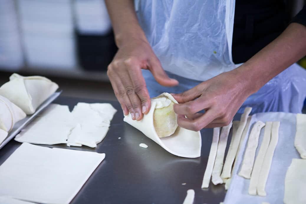 ידיים עוטפות תפוח מקולף בבצק עלים