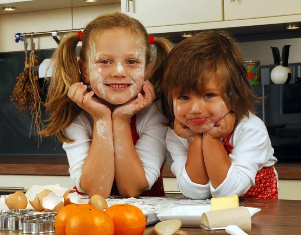 ילדות חמודות במטבח עם קמח על הפנים
