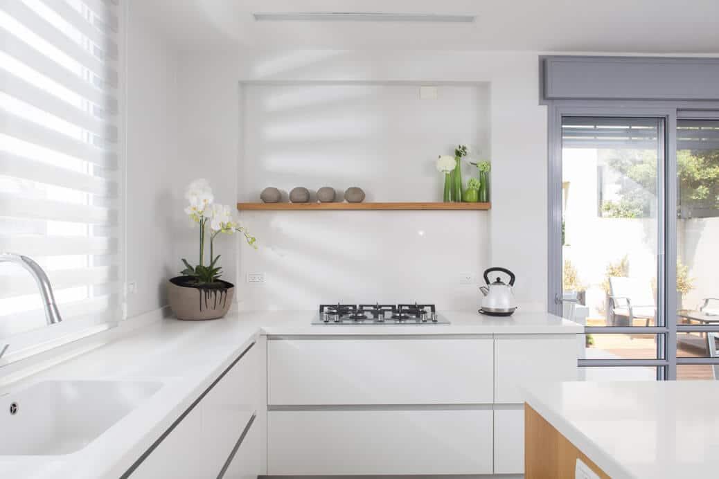 פינת מטבח לבן מודרני עם עזציץ סחלב ומדף עם חלוקי אבנים חומות