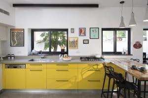 מטבח בצבע צהוב ושיש שחור עם בוצ'ר עץ מלא
