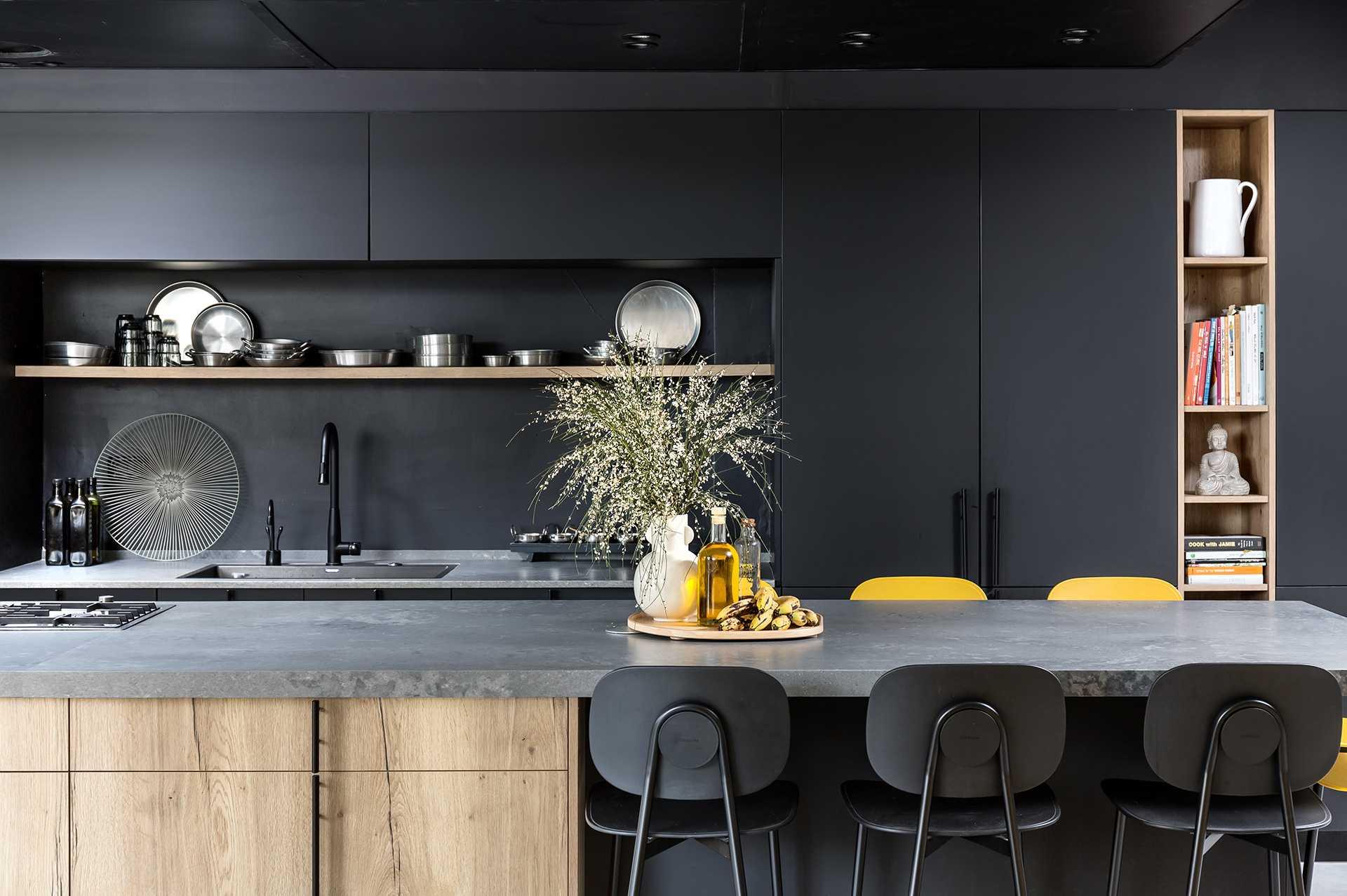 מטבח אפור עם כיסאות שחורים